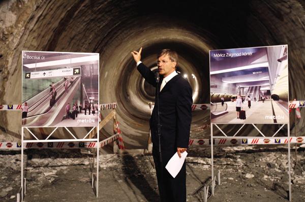 Demszky Gábor az akkor még épülő 4-es metrónál szemléltet az MTI fotóján